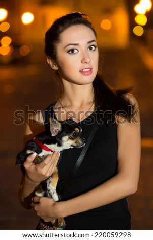Portrait of young brunette posing with a pet - stock photo