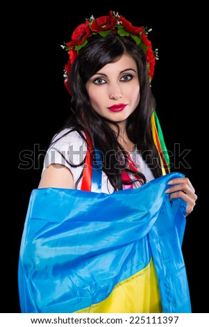 Portrait of young brunette posing with Ukrainian flag. Isolated on black