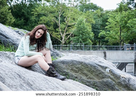 Portrait of young brunette sitting on the bouders in the park with hand on the head - stock photo