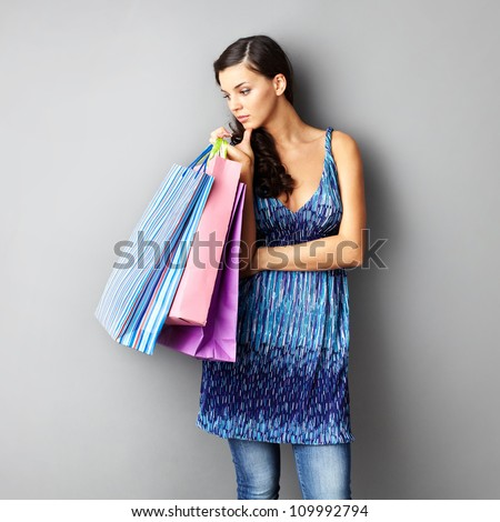 Portrait of young brunette with paperbags on grey background - stock photo