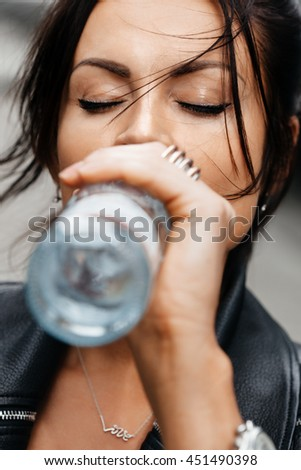 Portrait of young brunette woman drinking water from the bottle