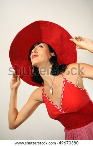 Portrait of young brunette woman holding her big red hat - stock photo