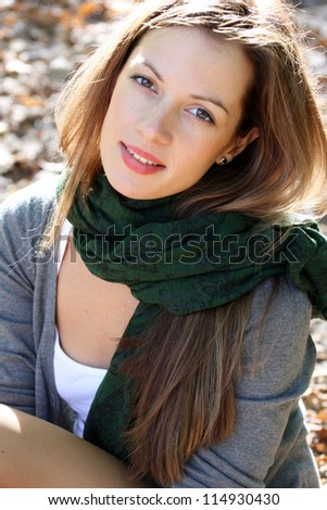 Portrait of young brunette woman in green scarf. - stock photo