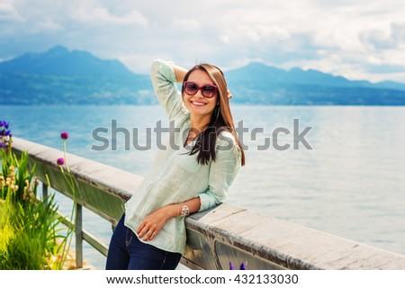 Portrait of young brunette woman resting outdoors by the lake, wearing sunglasses. Image taken on lake Geneva, Switzerland - stock photo