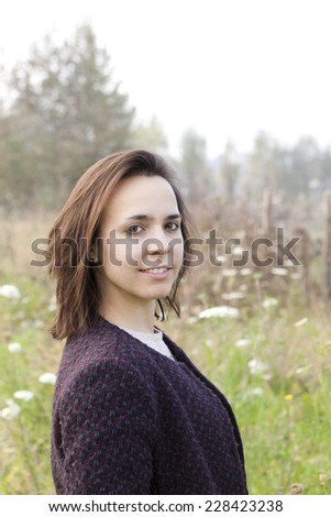 portrait of young brunette woman with coat with wildflowers field background - stock photo