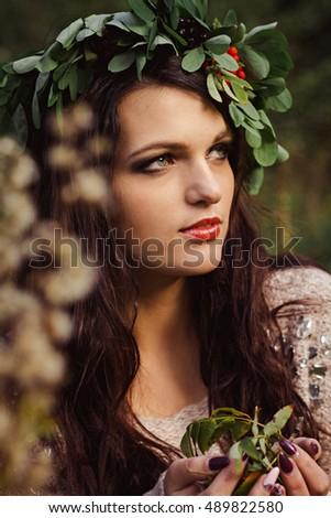 portrait of young brunette woman with outstanding forms, with a wreath of Rowan on the head and berries in his hands. Woman in autumn Park. Model plus size, model forms.