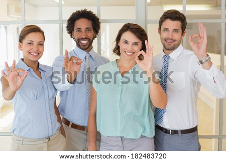 Portrait of young business colleagues gesturing okay sign in the office