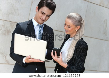 Portrait of young business couple reviewing information. - stock photo