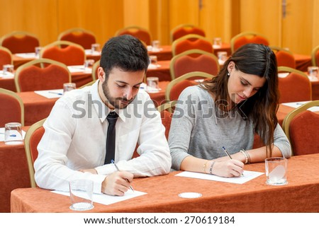 Portrait of young business couple taking notes in conference room.Couple sitting at table writing with pens with rows of seats in background. - stock photo