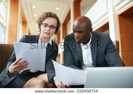 Portrait of young business man and woman sitting in cafe and discussing contract. Diverse businesspeople meeting in hotel lobby reading documents. - stock photo