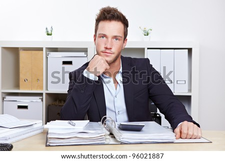 Portrait of young business man at desk in office