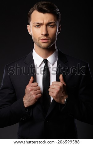 Portrait of young business man. Black background.