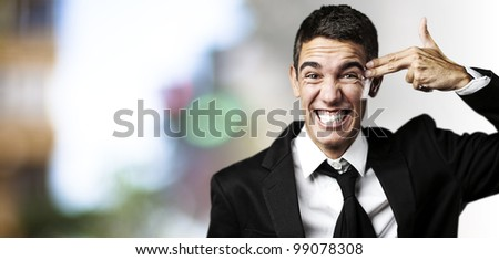 portrait of young business man doing suicide symbol at city - stock photo