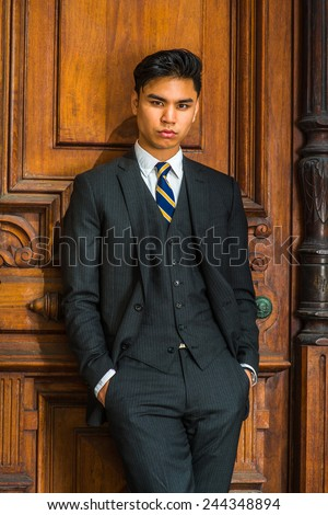 Portrait of Young Business Man. Dressing formally in three pieces black suit, patterned necktie, vest, hands in pockets, a young businessman standing by old fashion style office door, looking at you. - stock photo