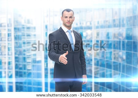 Portrait of young business man handshake gesturing, blue background. Concept of leadership and success - stock photo