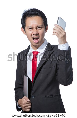 Portrait of young business man holding tablet and smartphone - stock photo