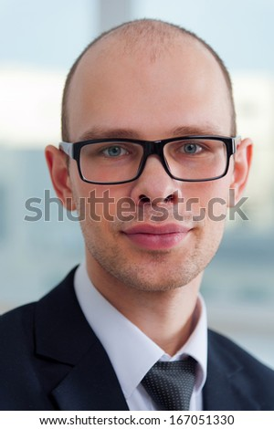 Portrait of young business man in office with view to window - stock photo