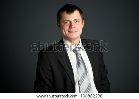 Portrait of young business man isolated over dark background