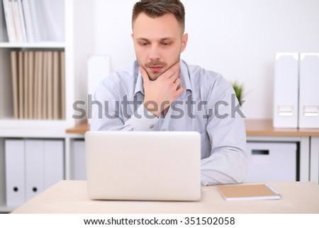 Portrait of young business man sitting at the desk on office background.