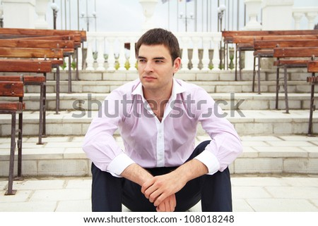 Portrait of  young business man sitting on steps looking away and thinking