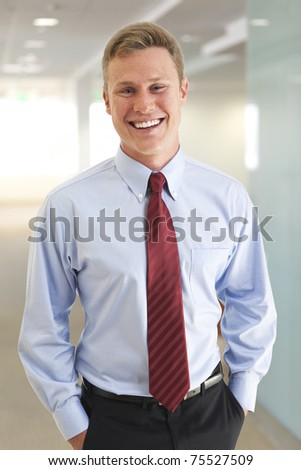 Portrait of young business man smiling with hands in pockets	 - stock photo