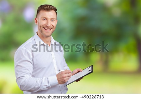 Portrait of young business man taking notes