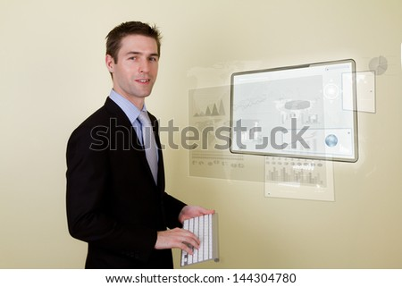 Portrait of young business man using a touch screen device with keyboard - stock photo
