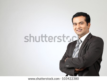 Portrait of young business man with folded hands against  background - stock photo
