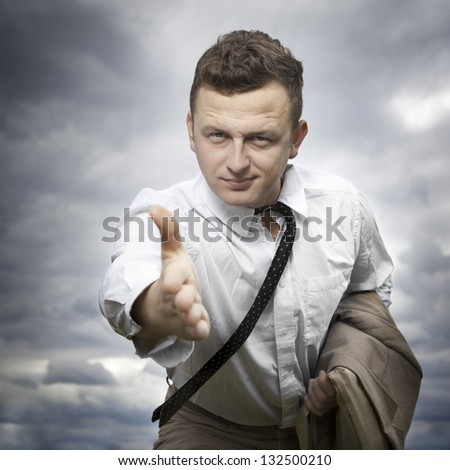 Portrait of young business man with hand outstretched to welcome you. Image on nature background. Sky and clouds in background. - stock photo