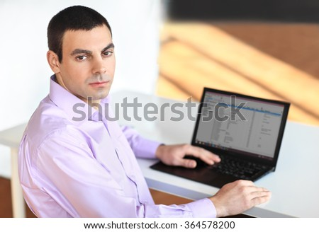 Portrait of young business man with laptop in the office
