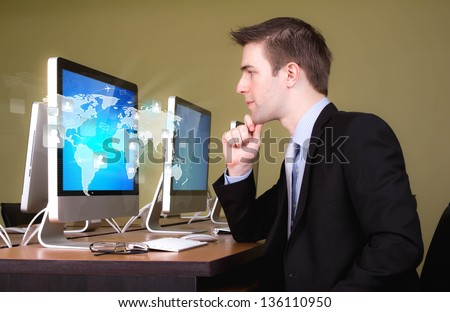 Portrait of young business man working in computer room with social network on world map - stock photo