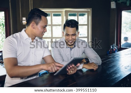 portrait of Young business owner and team partner with tablet in cafe - stock photo