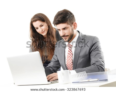 Portrait of young business people working together. Professional man sitting in front of laptop and typing on keyboard while businesswoman standing next to him. Isolated on white background.