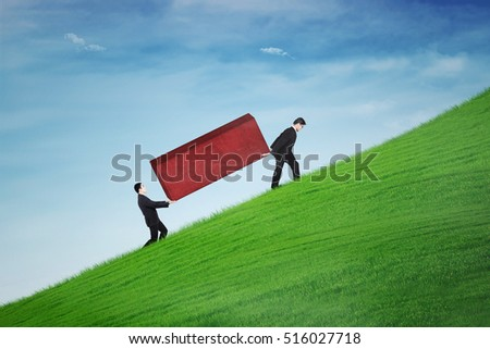 Portrait of young business team carrying a red block and walking uphill