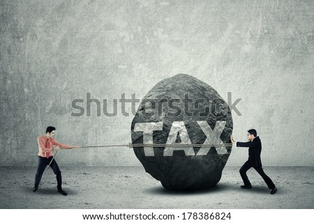 Portrait of young business teamwork try to move the big stone as a big obstacle - stock photo