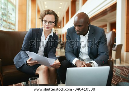 Portrait of young business woman and man sitting at hotel lobby discussing papers. Business people meeting in hotel lobby reading documents. - stock photo