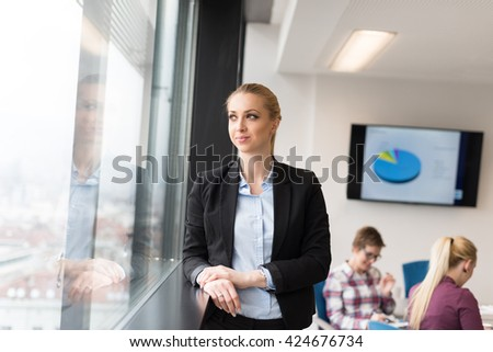 portrait of young business woman at modern startup office interior, team in meeting group in background - stock photo