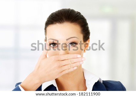 Portrait of young business woman covering with hand her mouth - stock photo