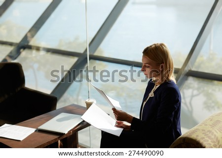 Portrait of young business woman holding some documents or paper in the hands sitting in light beautiful office hall, businesswoman examining paperwork - stock photo