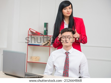 Portrait of young business woman looking at the camera and doing head massage to her colleague with closed eyes sitting at the desk in office with copy space, relationship at work concept - stock photo