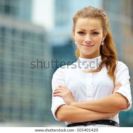 Portrait of young business woman on building background - stock photo