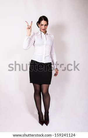 portrait of young business woman showing victory sign