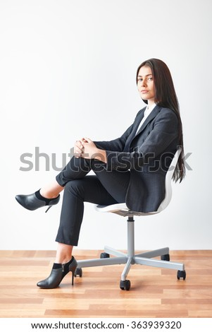 Portrait of young business woman sitting on chair in the office - stock photo