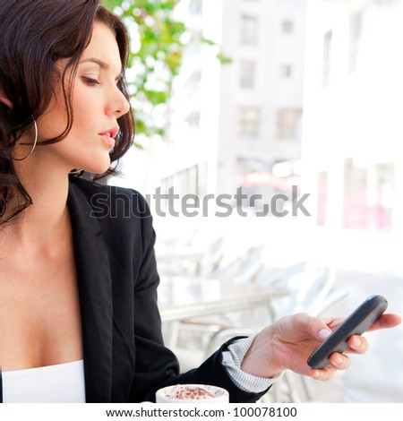 Portrait of young business woman sitting relaxed at outdoor cafe drinking coffee and chatting using her cell phone - stock photo