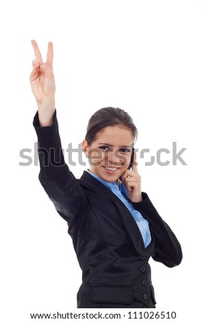 Portrait of young business woman smiling, showing victory sign and speaking at phone looking at the camera on white background - stock photo