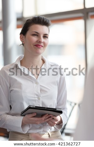 portrait of young business woman with tablet computer at modern office interior
