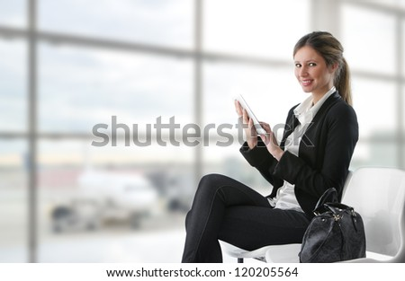 Portrait of young business woman working on digital tablet at airport - stock photo