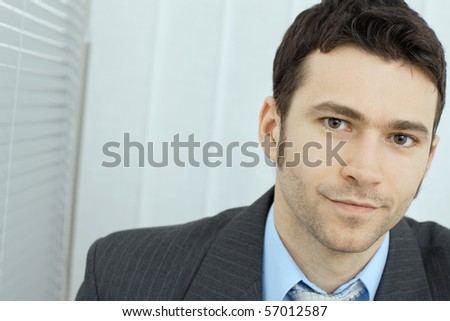 Portrait of young businessman at office, serious look. - stock photo