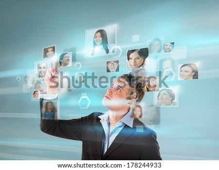 Portrait of young businessman choosing people for his business team using virtual computer interface