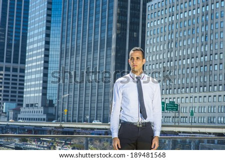 Portrait of Young Businessman. Dressing in a white shirt, a black tie, black pants, a young handsome guy is standing in the front of a busy business district, confidently looking forward.  - stock photo